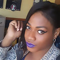 Chynal Lindsey. Black transgender woman in a gray sweater and purple lipstick.