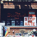 "Stonewall Inn. Many signs posted out front, including one reading  ""Stop the Hate."""