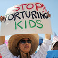 """woman wearing white shirt and straw hat holds a white sign with red, black and green lettering that reads, """"Stop Torturing Kids"""""""