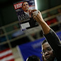"""Black person in dark top holds copy of Ebony high in their left hand. The cover features Barack Obama and reads """"In our lifetime."""""""