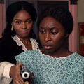 Cynthia Erivo and Janelle Monáe. Two Black women dressed in 1800s-styled clothing and holding a gun.