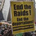 """A protestor holds up a yellow sign captioned """"End the Raids! End the deportations."""""""