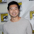 Simu Liu. Asian man with short dark hair wearing gray sweater standing in front of Comic-Con step and repeat.