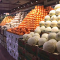 fruit aisle in supermarket with melons and oranges