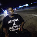"A Black man wearing a t-shirt that says ""Ferguson is everywhere"" protests at night."