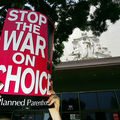"Hands holding a red sign that reads, ""Stop the war on choice."""