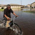 A Black man with gray hair wearing a black shirt and jeans bicycles through flooded streets in Texas
