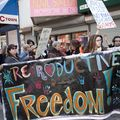 """A multiracial group of women hold up a colorful sign that says, """"Reproductive Freedom!"""""""