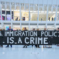 "A group of protestors hold a sign that reads, ""U.S. Immigration Policy is a Crime"""