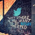 """Brick wall with chalk sign that reads, """"Tweet others as you want to be tweeted"""" with a blue bird."""