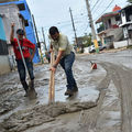 Two people standng in the muddy rode in Puerto Rico, shovels in hand, colorful buildings and blue sky behind them