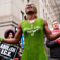 """Patricia Okoumou. Black woman wearing a green dress that reads, """"I really care, why won't u?"""""""