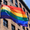 Rainbow pride flag flies in front of brick building and blue sky