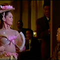 Nancy Kwan. Scene featuring Asian woman wearing hat with pink flowers and elaborate costume with a bra fan, in a restaurant.
