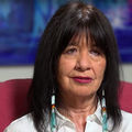 Joy Harjo. Native American middle aged woman with shoulder length dark hair wearing white blouse and colorful bead earrings.