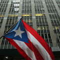 Red, white and blue Puerto Rican flag in front of a high rise office building