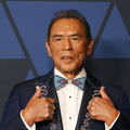 Wes Studi. Older Native American man with short dark hair wearing blue tux jacket and white shirt.