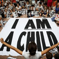 """Children are gathered around a large black and white sign that reads, """"I Am a Child."""""""