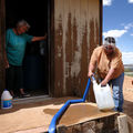 a woman fills a plastic container of water as another women looks on in the Navajo Nation