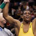 Anthony Robles. Young Black man wearing yellow wrestling uniform and being named winner by older White man.