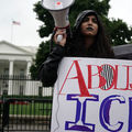"""Latinx person with dark hair and blue lipstick wears black raincoat and holds a white megaphone and sign that reads """"Abolish ICE."""""""