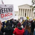 """Protester in front of the U.S. Supreme Court holds a sign that reads, """"Defend DACA."""""""