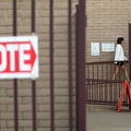 """A red and white """"vote"""" sign is in the foreground, with a voter walking to the polls in the distance."""