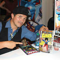 John Leguizamo.Latinx man wearing black hat and vest and blue shirt holding up comic books.