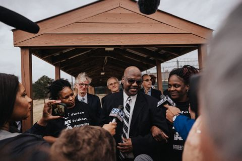Curtis Flowers. Black man with bald head, dark glasses, dark suit, white shirt and black-and-white tie surrounded by people and reporters.