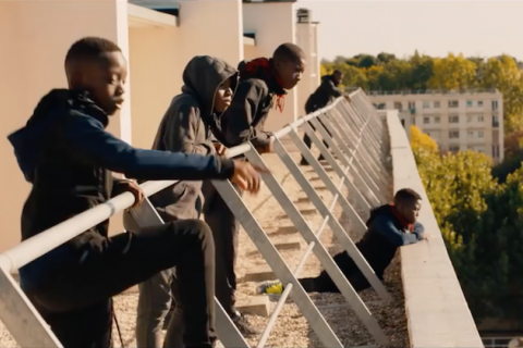 Les Misérables. Black boys stand on ledge, look out over city.