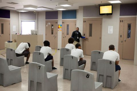 A group of young people wearing white t-shirts and dark shorts are shown seated inside of a juvenile detention center with their backs to the camera.