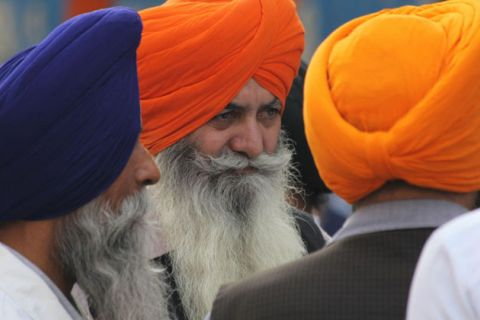 People in blue, orange and yellow turbans with long beards look into the distance.
