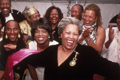 Toni Morrison. Older Black woman with gray locs pulled back wearing black top and surrounded by clapping Black women.