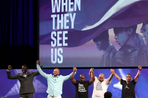 Yusef Salaam, Kevin Richardson, Anton McCray, Raymond Santana and Korey Wise. Five men of color hold hands on stage with movie image projected behind them on screen.