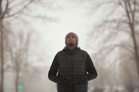 Black man with beard standing in snowy, tree-lined street wearing knit cap, black winter coat, with hands in pockets.