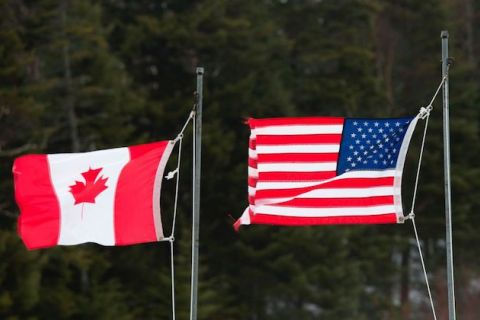 Red and white Canadian flag and red, white and blue American flag fly next to each other at the U.S.-Canada border.