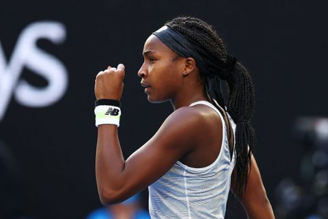Coco Gauff. Young Black woman on tennis court wearing long braids, blue headband, white tank top and white and black wristband.