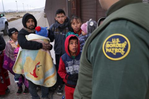 A group of adults and small children gather in front of a a guard wearing a green Customs and Border Protection uniform.