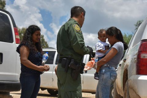 One woman holding an infant and another woman with dark hair stand next to a border patrol agent wearing a green uniform