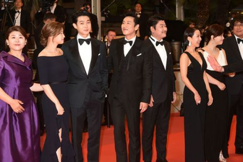 Cast of Parasite. Asian men and women standing on red carpet with one person wearing a purple gown and everyone else dressed in black gowns and tuxedos.
