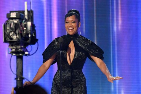 Regina King. Black woman with dark hair pulled into a high ponytail wearing a black gown while standing in front of a camera.