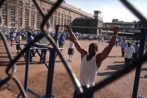 Black man in beige prison uniform does pull-ups outside in a prison yard.