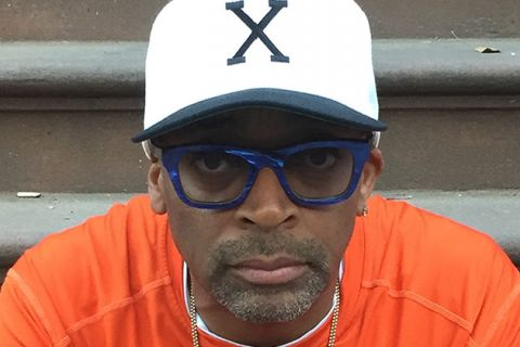 "Spike Lee. Black man wearing white ""X"" cap with blue glasses and orange t-shirt."