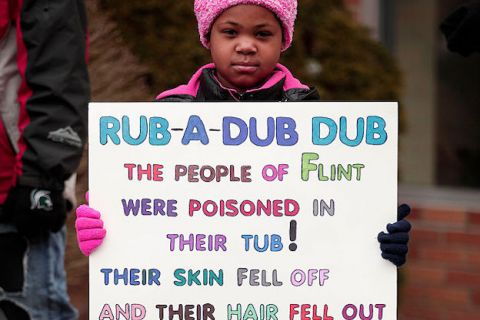 Young Black girl wearing a pink hat and matching pink coat holds a sign protesting the Flint water crisis in Flint, Michigan.