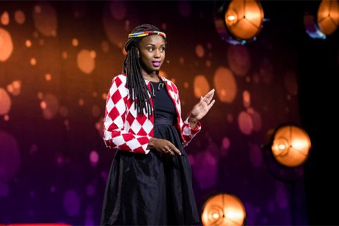 Wanuri Kahiu. Black woman with long braids wearing black dress and red-and-black checked jacket with beads around her head.