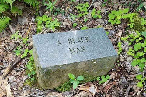 "Gray stone in a wooded area with the engraving ""A Black Man."""
