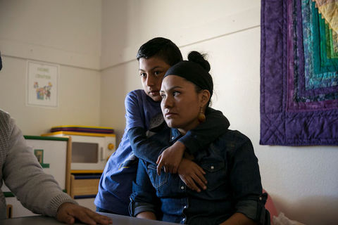 Latinx woman wearing denim shirt sits as her young son stands behind her with his arms wrapped around her shoulders.