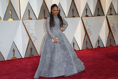 Ava DuVernay. Black woman with long brown locs wearing silver gown on red carpet standing in front of Oscar statues.