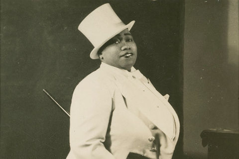 Gladys Bentley. Black woman wearing white top hat and white tuxedo with cane.