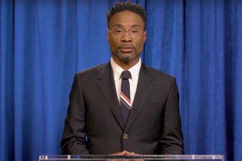 Billy Porter. Black man with short dark hair wearing dark suit jacket, blue and red tie with white shirt and glasses, standing in front of blue curtain.